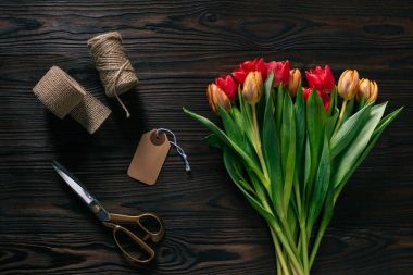 top view of arranged tulips, rope, scissors and ribbon for decoration on wooden surface