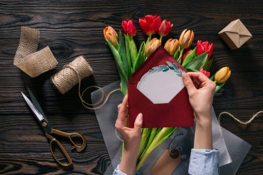 cropped shot of woman with postcard in hands and tulips in wrapping paper on wooden tabletop
