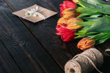 close up view of bouquet of tulips, postcard and rope on wooden tabletop