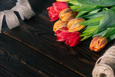 close up view of bouquet of tulips, ribbon and rope on wooden tabletop