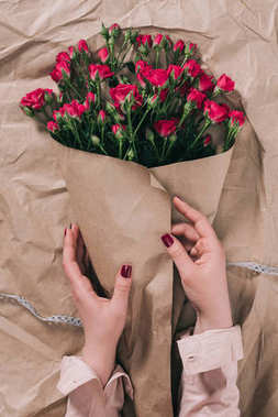 partial view of female hands and bouquet of roses in craft paper