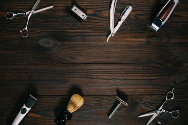 top view of arrangement of various barber tools on wooden tabletop