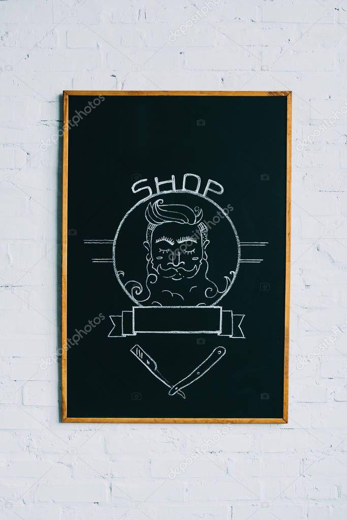 close up view of drawn emblem of bearded man on blackboard
