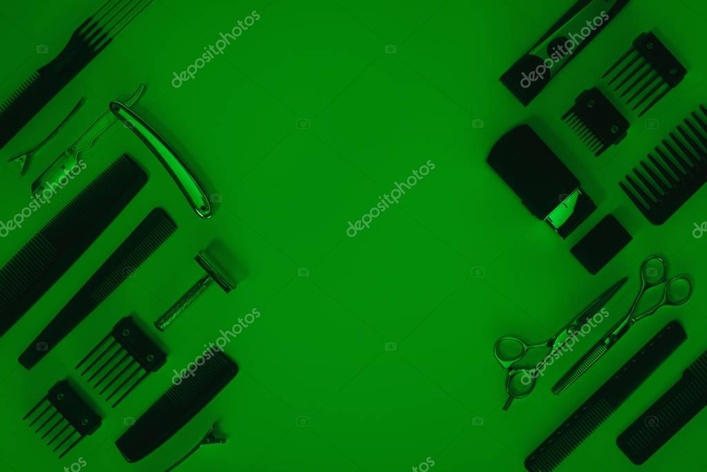 top view of arrangement of various barber tools isolated on green