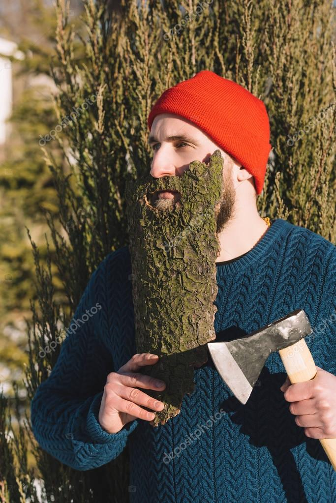man with beard made of wood bark and axe in hand looking away outdoors