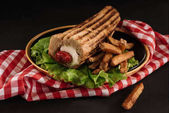 Fotografie Detailní záběr lahodné francouzské hot dog s hranolky na desce izolované na černém