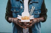 Photo cropped shot of african american man in denim jacket holding box of chinese noodles