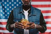 Fotografie oříznutý snímek americký muž, který držel burger proti usa vlajka