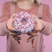Photo cropped shot of woman showing tasty glazed doughnut at camera