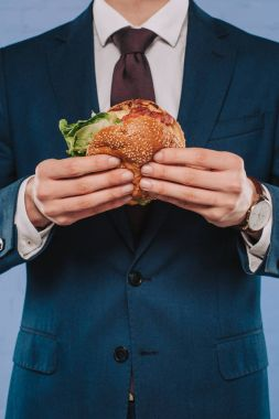 Cropped shot of businessman in formal suit holding burger stock vector