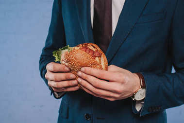 cropped shot of businessman in suit holding burger