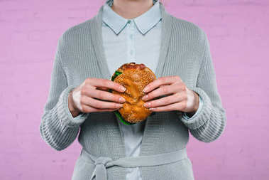 cropped shot of woman in sweater and shirt holding burger