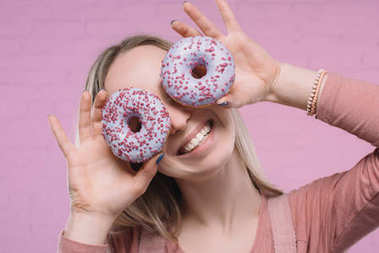 playful young woman covering eyes with doughnuts