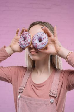 young woman covering eyes with doughnuts in front of pink brick wall