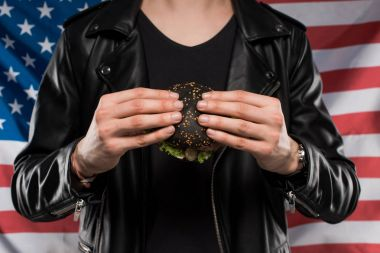 cropped shot of man in leather jacket holding black burger against usa flag