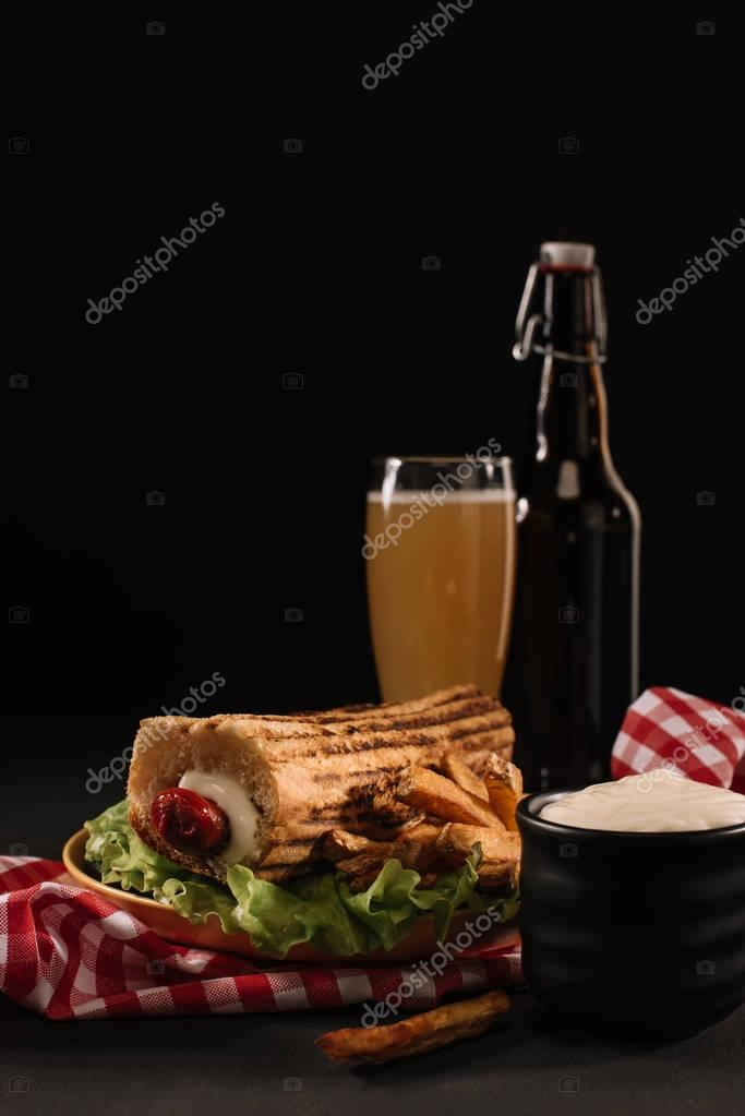 delicious french hot dog on plate with bottle and glass of beer isolated on black
