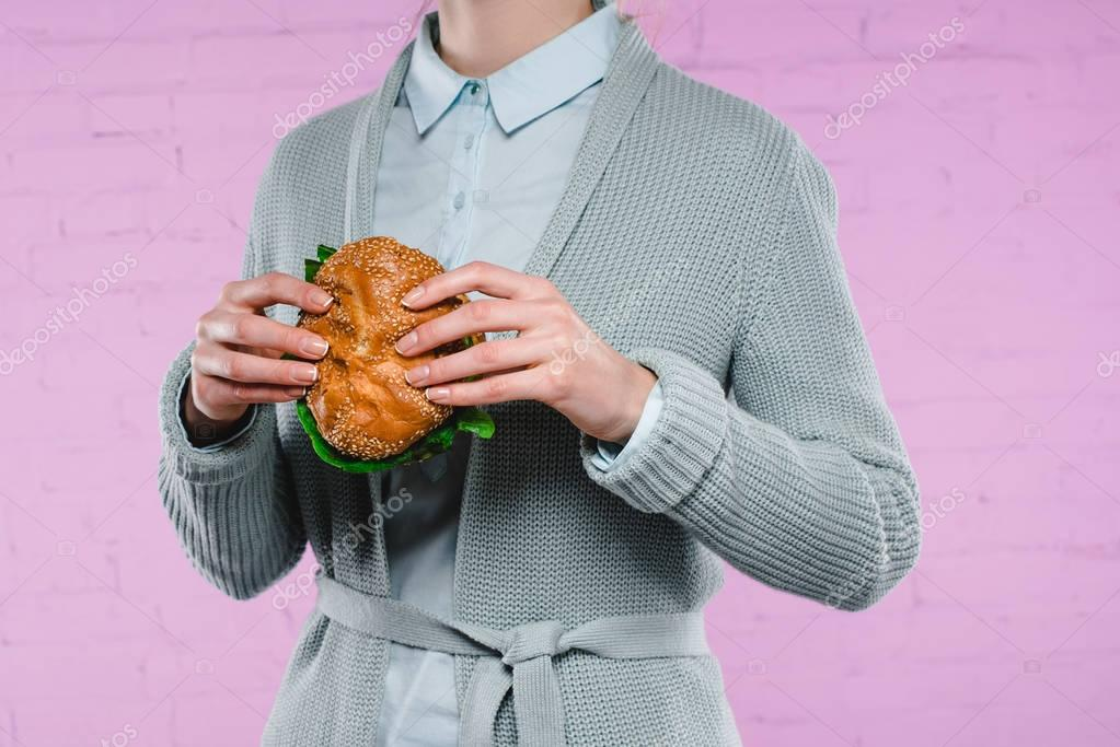 cropped shot of woman in sweater and shirt holding tasty burger