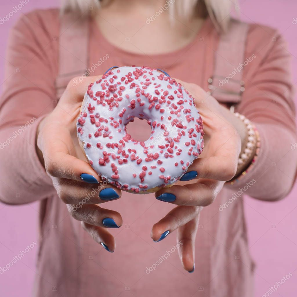 cropped shot of woman showing tasty glazed doughnut at camera