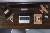 pohled shora na stolní počítač, notebook a kancelářské potřeby na dřevěný stůl