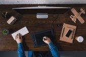 pohled shora osoby pomocí grafického tabletu a psaní na klávesnici na pracovišti