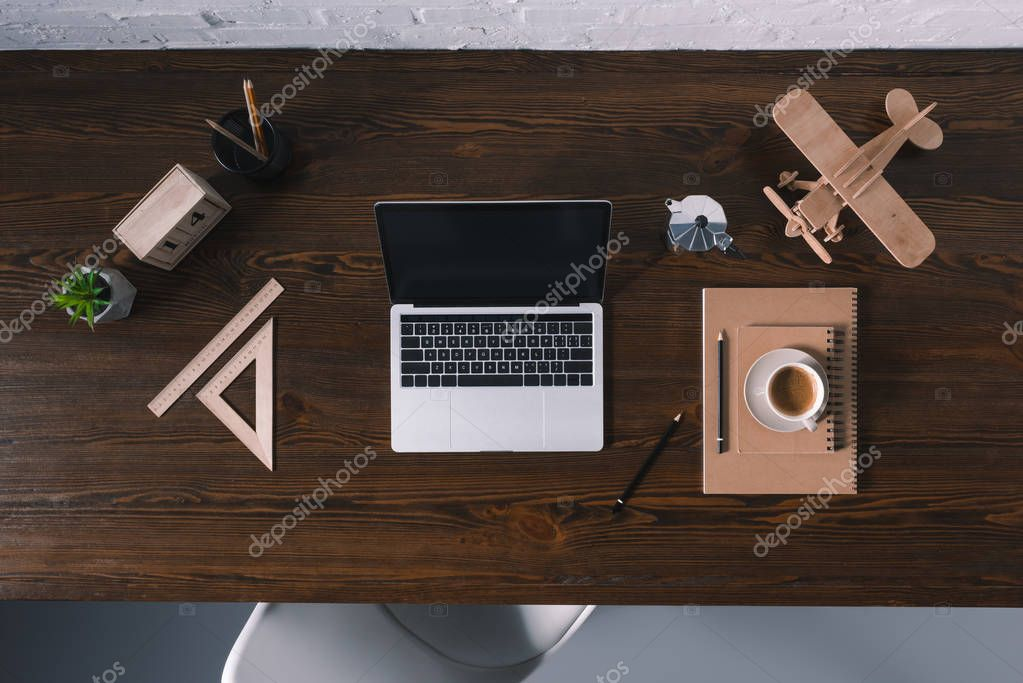top view of laptop with blank screen and office supplies on wooden table