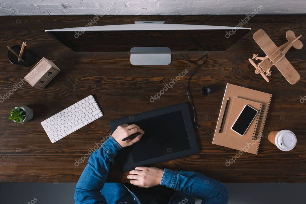 partial top view of person using graphics tablet while sitting at workplace