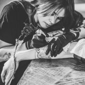 Fotografie Black and white photo of concentrated female artist in gloves working on arm piece tattoo in studio