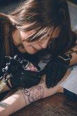 Koncentrált női előadó dolgozik a kar darab tattoo studio kesztyű