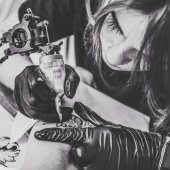 Fotografie Black and white photo of woman tattoo during tattooing process