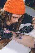 Tattoo umělec při tetování proces žena