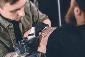 Tattoo umělec a vousatý muž při tetování proces ve studiu