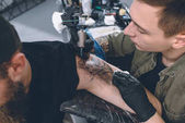 Vousatý muž a tetování naučit během tetování proces ve studiu