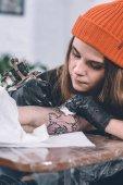 Fotografia Ragazzo e master femminile tatuaggio durante il processo di tatuaggio in studio