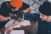 Fotografia Giovane e femminile tatuaggio master durante il processo di tatuaggio in studio