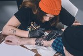 Chlapce a ženy tetování master během tetování ve studiu