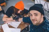 Fotografia Uomo sorridente e tatuaggio master durante il processo di tatuaggio in studio