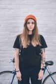 Fotografie Junges Mädchen mit tätowierten Arm stand neben dem Fahrrad durch die Wand