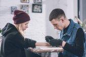 Fotografia Maestro del tatuaggio in guanti lavorare su braccio pezzo in studio