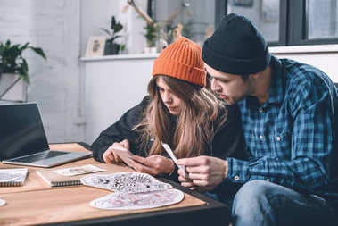 Man and woman choosing tattoo design in studio