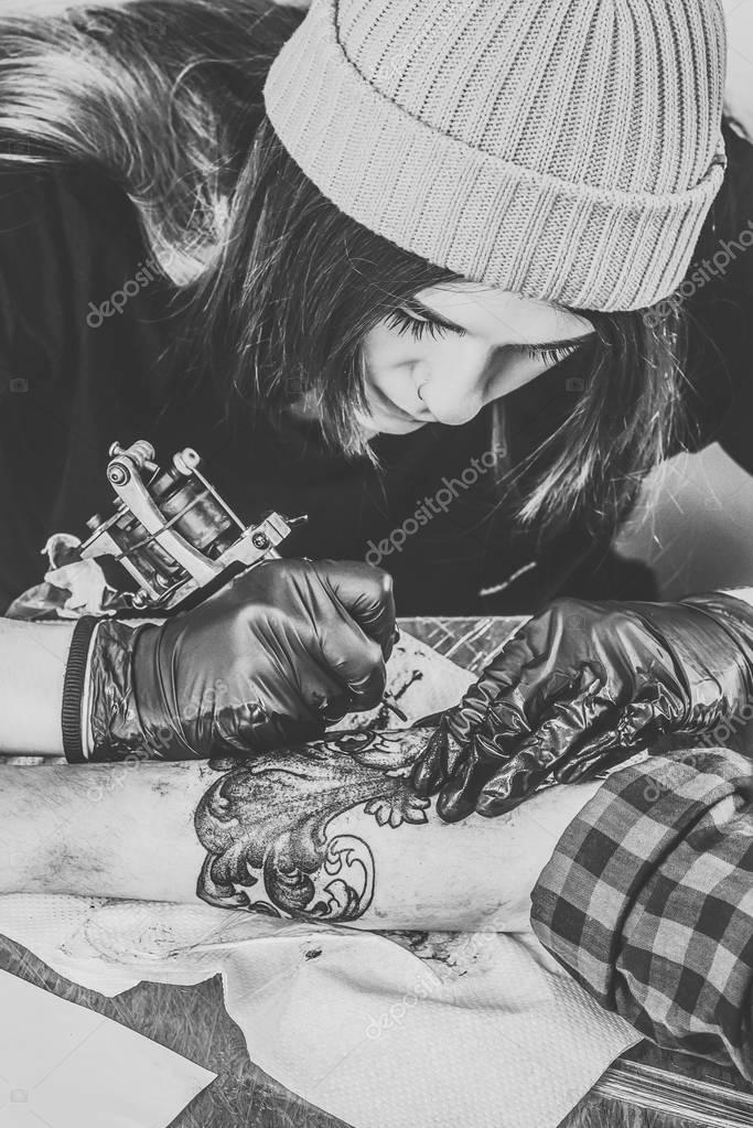Black and white photo of woman tattoo artist in gloves working on arm piece