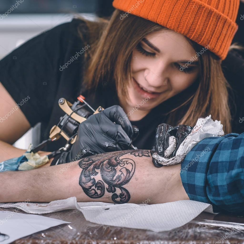 Close-up view of female tattoo master in gloves working on arm piece