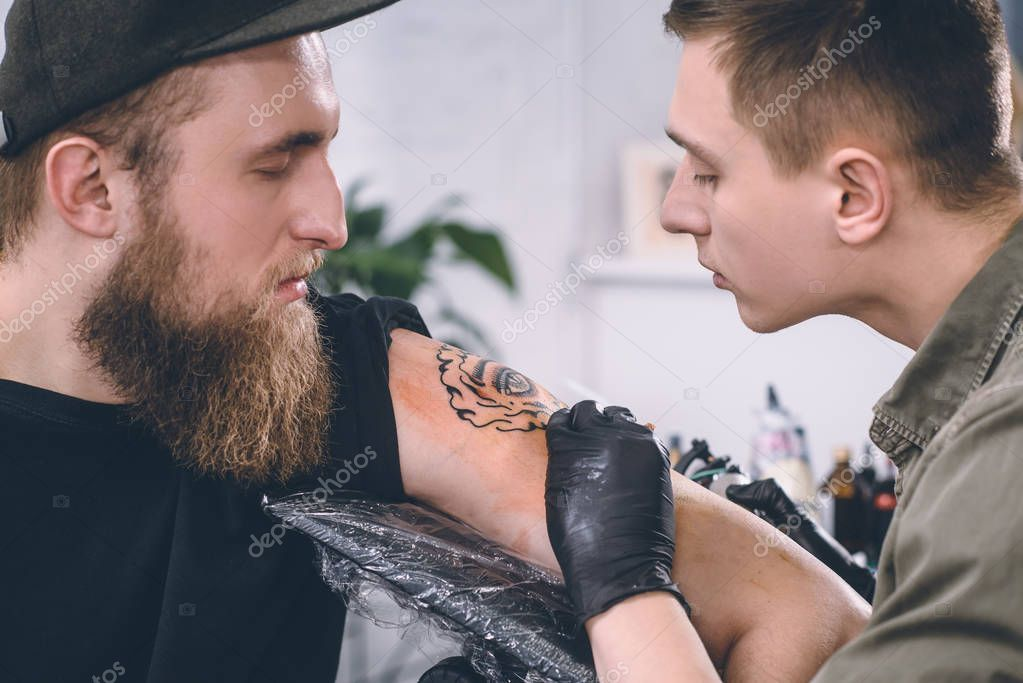 Bearded man and tattoo master during tattoo process in studio