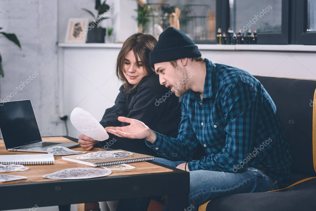 Girl and guy discussing tattoo design in studio