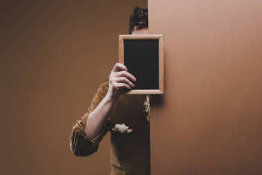 Man in stylish clothes holding empty frame isolated on brown