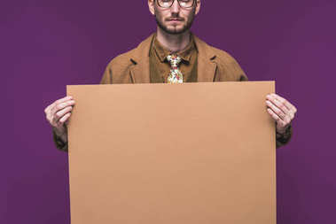 Stylish man in vintage styled clothes holding empty paper isolated on purple