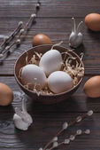 Fotografie chicken eggs in bowl with straw and easter rabbits on wooden table