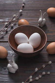 Fotografie chicken eggs in bowl and easter rabbits on wooden table
