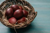 Fotografie easter basket with painted eggs and straw on table