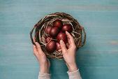 ořízne obraz žena uvedení velikonoční vejce v košíku