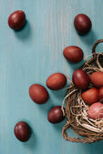 Fotografie top view of easter basket with painted eggs and straw on table
